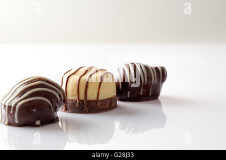 Three bonbons black and white chocolate on a white table. Front view. Close up. Horizontal composition. - Stock Photo