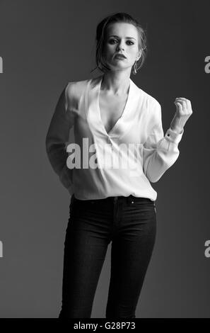 Contemporary woman in black and white aesthetic. Portrait of modern elegant woman against grey background - Stock Photo