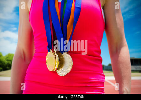 Composite image of portrait of sportswoman chest with medals - Stock Photo