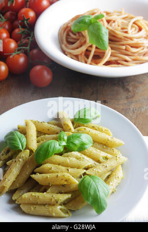 Two plates of pasta with pesto and tomato sauce - Stock Photo