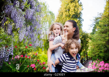 Mother with daughter and son walking in a summer park. They are all very fun. Mom carries her daughter on her shoulders. - Stock Photo