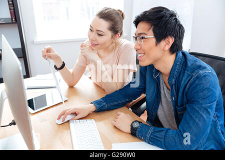 Smiling young man and woman working with computer in office together - Stock Photo