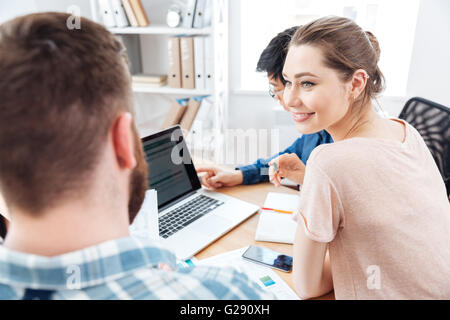 Happy attractive young woman sitting and working with two young businessmen in office - Stock Photo