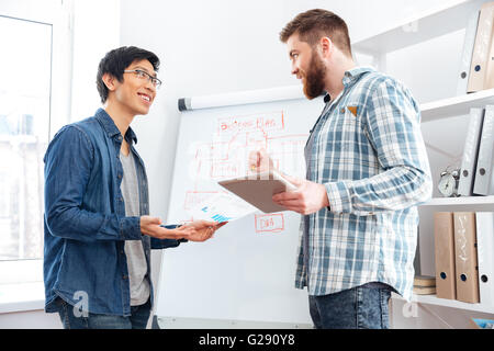 Two confident young businessmen making business plan using tablet and flipchart in office - Stock Photo