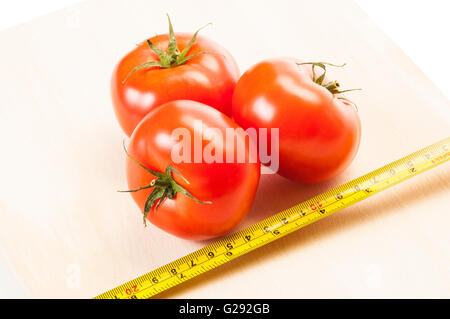 Measure the calories of three red tomatoes for a diet, with a centimeter on a wooden board and white background - Stock Photo