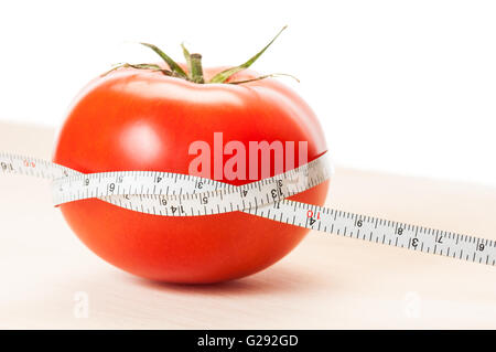 Loose weight with perfect red tomatoes diet concept. Wooden board, red tomato, white centimeter and background. - Stock Photo