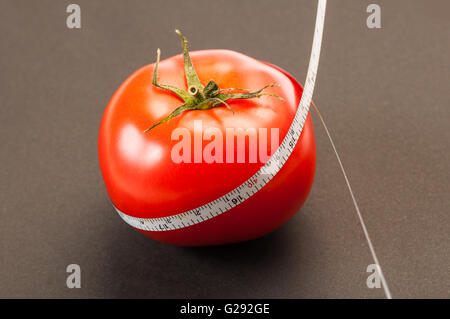 A diet using red tomatoes concept using a white thin centimeter to measure the calories. On a dark background - Stock Photo