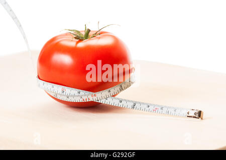 Measure calories of a perfect red tomato with a centimeter. Diet concept made of tomato, meter, wooden board and - Stock Photo