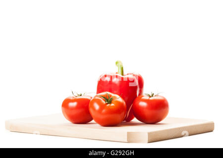 Beautiful red tomatoes, a fat red pepper on wooden board isolated on white background. - Stock Photo