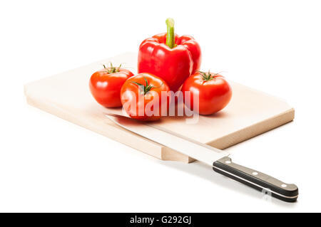 Three perfect red tomatoes, one fat red pepper, steel knife and wooden board, all isolated on white background. - Stock Photo