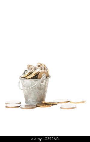 Bunch of golden coins in a small bucket isolated on white background - Stock Photo
