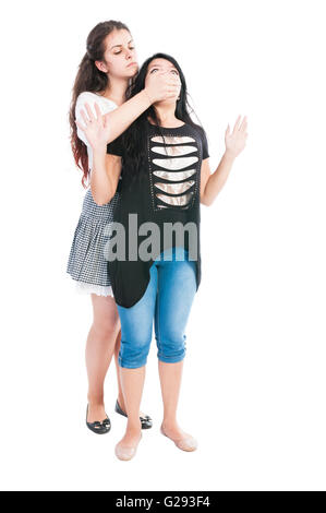 Taller girl bullying her friend by covering the mouth with hand and pulling her hair - Stock Photo
