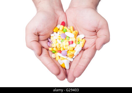 A man is holding a lot of different pills in both his hands - Stock Photo