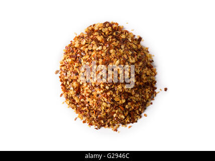 A pile of crushed red pepper flakes on white with slight shadow. - Stock Photo