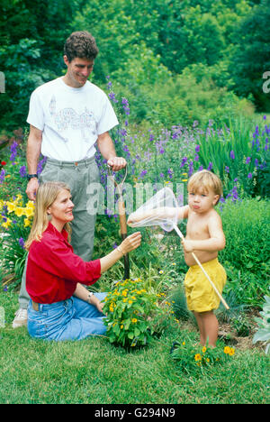 Family and young boy in garden with butterfly net makes a face at camera, Missouri, USA - Stock Photo