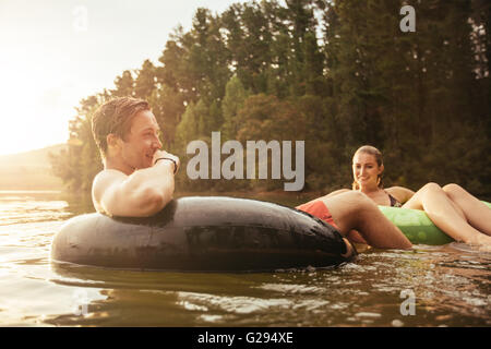 Portrait of happy young man in lake on inflatable ring with his girlfriend. Young couple relaxing in water on a - Stock Photo