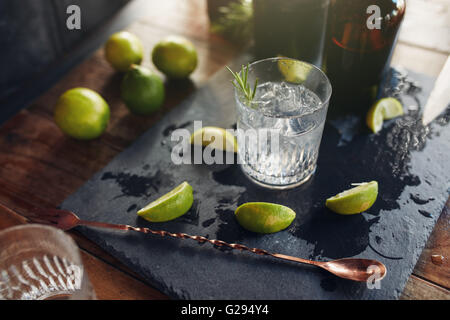 Close up of fresh made cocktail drink with lemon slices and spoon on the board. - Stock Photo