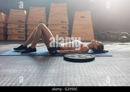 Side view shot of fitness woman resting on exercise mat with a heavy weight plate on floor. Female athlete lying - Stock Photo