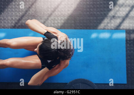 Overhead view of female working out at the gym. Muscular young woman doing sit ups on an exercise mat. - Stock Photo