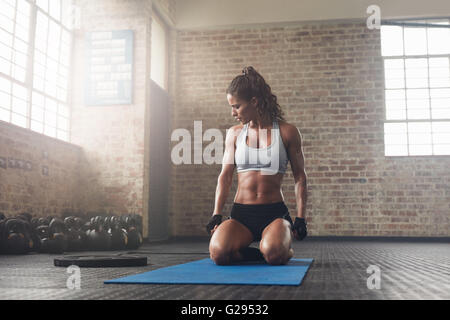 Indoor shot of  fitness young woman sitting on yoga mat at gym. Muscular young female athlete taking a break from - Stock Photo