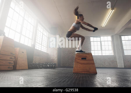 Side view image of fit young woman doing a box jump exercise. Muscular woman doing a box squat at the cross fit - Stock Photo