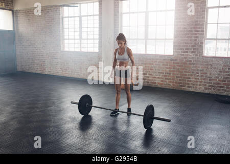 Full length portrait of muscular young woman standing at gym with barbells on floor. Strong crossfit female at gym. - Stock Photo