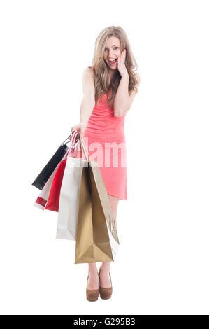 Amazed and surprised shopping girl on white background - Stock Photo