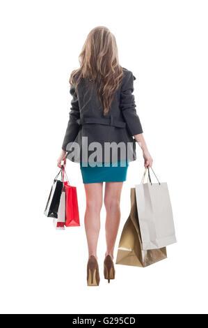 Beautiful shopping girl walking. Photo taken from behind on white background - Stock Photo