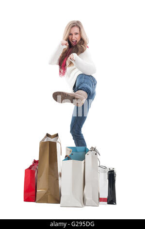Young, blonde and beautiful shopping woman in in fighting position - Stock Photo