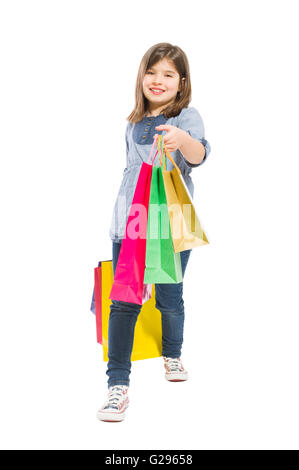 Young shopping girl walking with gift bags isolated on white background - Stock Photo