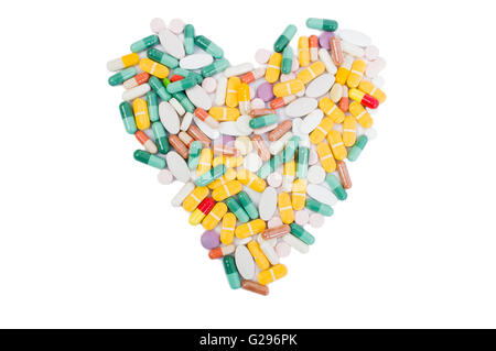 Heart shape made of pills isolated on white table - Stock Photo