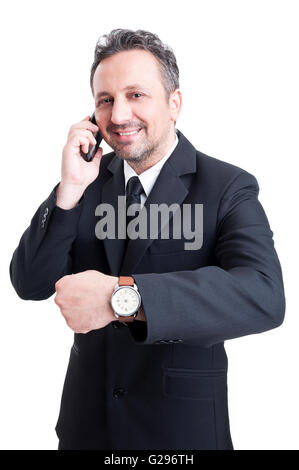 Modern business man showing time for meeting or profit gesture talking on the phone - Stock Photo