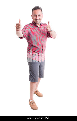 Cheerful man showing thumbs up. He wears shorts and short sleeve shirt - Stock Photo