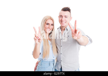 Lovely young couple showing peace or victory sign on white studio background - Stock Photo