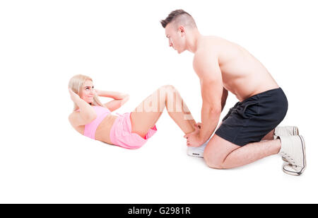 Personal trainer helping fitness woman to make crunches isolated on white - Stock Photo