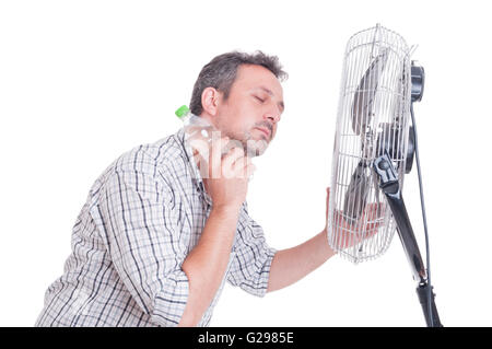 Man cooling down in front of blowing fan holding a bottle of cold water on the neck - Stock Photo