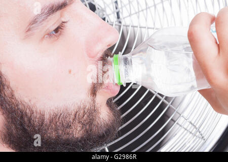 Closeup with thirsty man drinking water  and cooling down with blowing fan - Stock Photo