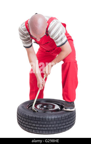 Hard-working mechanic changing car wheel tire isolated on white - Stock Photo