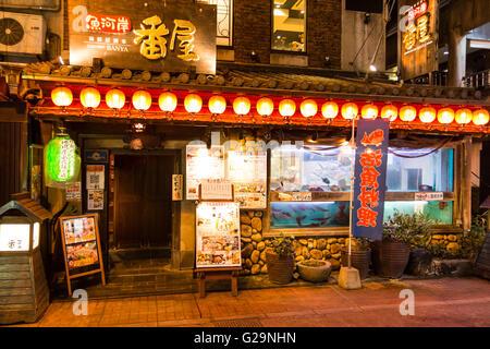 Japan, Kumamoto city centre. Evening. Front of traditional style Japanese seafood restaurant, Uogashi Banya, with - Stock Photo