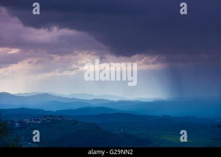 Cloudy rainy sky over mountain valley. Tyscany, Italy - Stock Photo