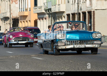 A 1958 Pontiac Super Chief (Blue Car) and a 1950 Chevrolet Bel Air (Purple Car) travelling along the Malecón in - Stock Photo