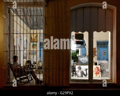 A shop in Trinidad, Cuba selling art work with the owner sitting inside on a rocking chair. - Stock Photo