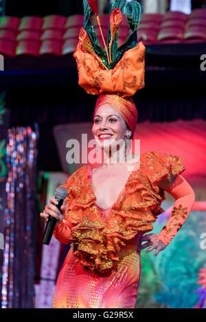 A Cuban Salsa singer in colourful traditional dress performing on stage at a hotel in Varadero. - Stock Photo