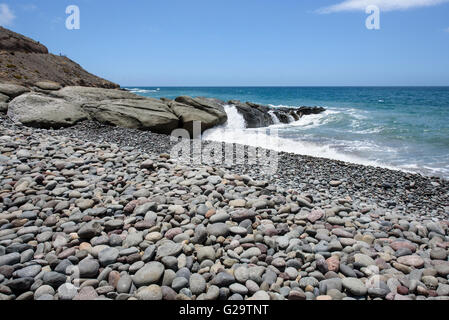 Waves breaking over rocks on the beach at Pasito Blanco in the south of Gran Canaria - Stock Photo