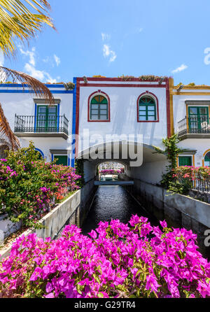 Beautiful purple Bougainvillea flowers adorn the front of a house in Puerto de Mogan in Gran Canaria - Stock Photo