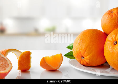 Group of oranges on a plate and sections on white glass table in the kitchen. Horizontal composition. Front view - Stock Photo