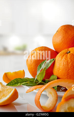 Group of oranges on a plate and sections on white glass table in the kitchen. Vertical composition. Front view - Stock Photo
