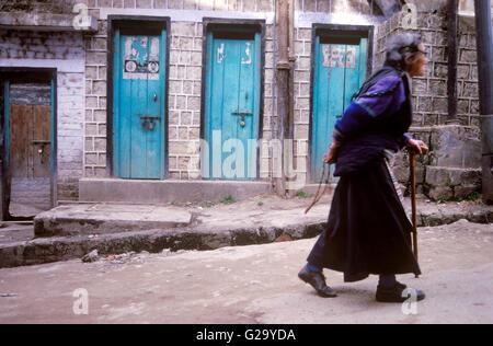 An elderly Tibetan woman walks the streets of McLeod Ganj while holding her prayer beads behind her back.Dharamsala, - Stock Photo