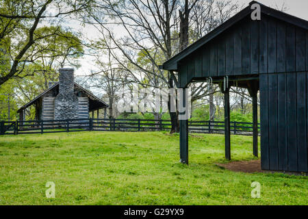 A Blacksmith's wooden horse stall in foreground with log cabin on farm surrounded by green grass, trees & black - Stock Photo