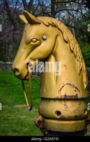 An old and weathered cast iron horse hitching post from the 19th century stands guard and noble on stately grounds - Stock Photo